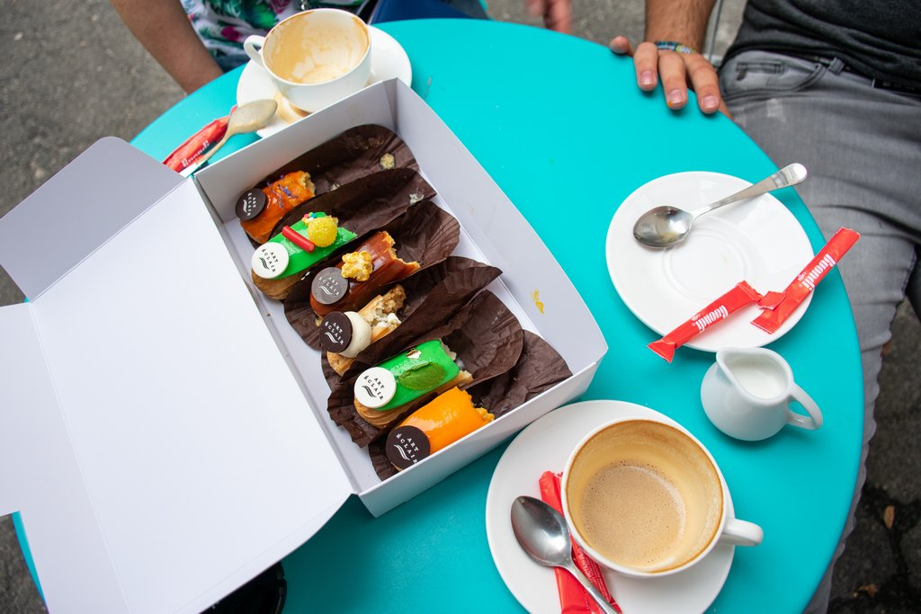 """<img src=""""finished eclairs.png"""" alt=""""a box of finished eclairs on a coffee shop table"""">"""